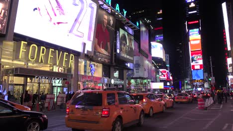 Nighttime-crowds-of-people-taxis-and-bright-neon-advertisements-in-Times-Square-New-York-City