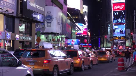 Nighttime-crowds-of-people-taxis-and-bright-neon-advertisements-in-Times-Square-New-York-City-1