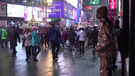 Crowds-of-people-walk-past-a-mime-in-New-York-s-Times-Square