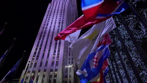 Tilt-Up-Shot-Para-Revelar-El-Rockefeller-Center-En-La-Ciudad-De-Nueva-York-Por-La-Noche-Con-Banderas-Ondeantes