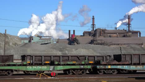 Global-warming-is-suggested-by-shots-of-a-steel-mill-belching-smoke-into-the-air-with-railcars-foreground