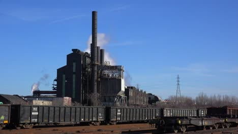 Global-warming-is-suggested-by-shots-of-a-steel-mill-belching-smoke-into-the-air-with-railcars-foreground-1
