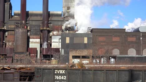 Global-warming-is-suggested-by-shots-of-a-steel-mill-belching-smoke-into-the-air-with-railcars-foreground-2