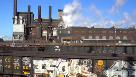 Global-warming-is-suggested-by-shots-of-a-steel-mill-belching-smoke-into-the-air-with-railcars-foreground-3