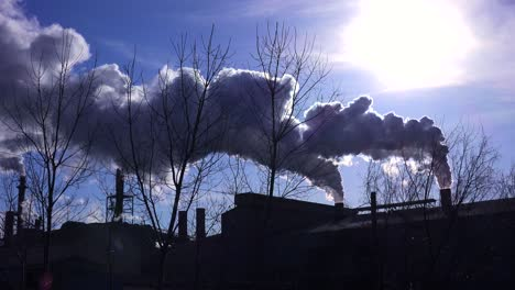 Global-warming-is-suggested-by-shots-of-a-steel-mill-belching-smoke-into-the-air-with-sun-background