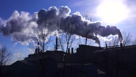 Global-warming-is-suggested-by-shots-of-a-steel-mill-belching-smoke-into-the-air-with-sun-background-1