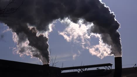 Global-warming-is-suggested-by-shots-of-a-steel-mill-belching-smoke-into-the-air-with-sun-background-2