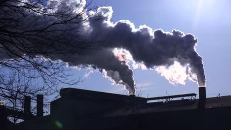 Global-warming-is-suggested-by-shots-of-a-steel-mill-belching-smoke-into-the-air-with-sun-background-3