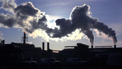 Global-warming-is-suggested-by-shots-of-a-steel-mill-belching-smoke-into-the-air-with-sun-background-6