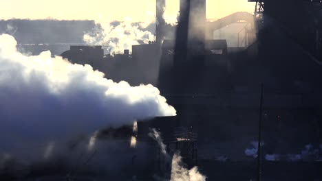 Establishing-shot-of-a-busy-steel-mill-with-smoke-belching-suggests-global-warming