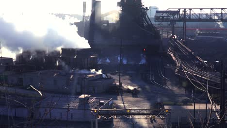 Establishing-shot-of-a-busy-steel-mill-with-smoke-belching-suggests-global-warming-2
