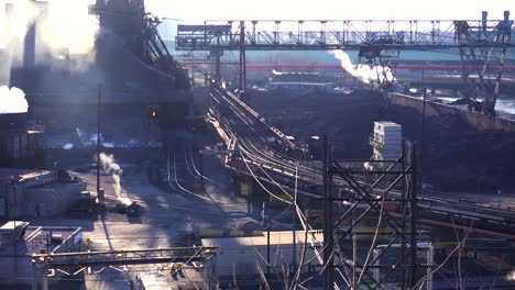 Panning-shot-of-a-busy-steel-mill-with-smoke-belching-suggests-global-warming
