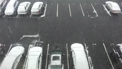 Un-Alto-ángulo-De-Vista-De-La-Nieve-Cayendo-En-Un-Estacionamiento-Con-Autos