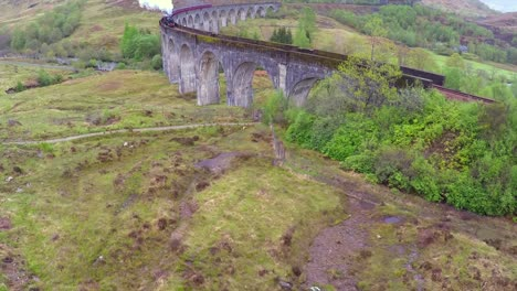 An-amazing-aerial-view-over-the-Glenfinnian-Viaduct-in-Scotland-with-steam-train-passing