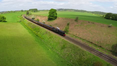 An-aerial-of-a-steam-train-as-it-passes-through-the-English-countryside-at-high-speed