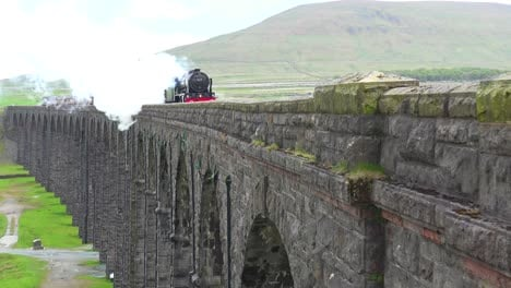 A-steam-train-passes-over-a-long-stone-viaduct-bridge-in-the-English-countryside
