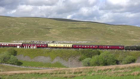 A-steam-train-passes-along-a-hillside-in-the-English-countryside