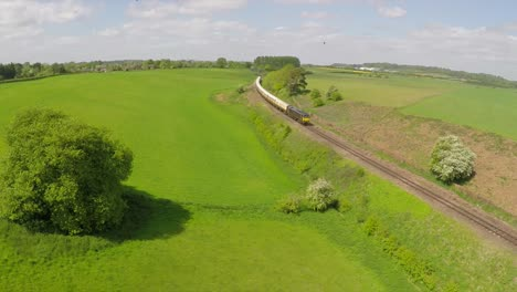 An-aerial-of-a-diesel-passenger-train-as-it-passes-through-the-English-countryside-at-high-speed