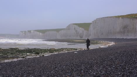 A-woman-walks-along-the-White-Cliffs-of-Dover-near-Beachy-Head-in-Southern-England