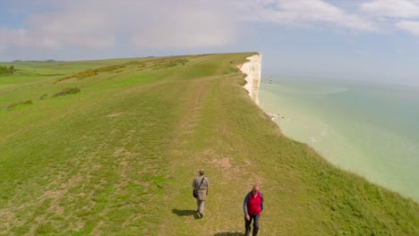Aerial-shot-of-people-walking-along-the-White-Cliffs-of-Dover-at-Beachy-Head-England