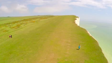 Vista-Aérea-shot-of-people-walking-along-the-White-Cliffs-of-Dover-at-Beachy-Head-England-1
