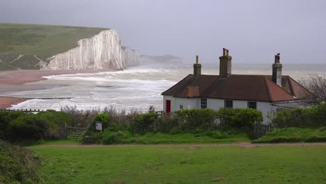 Establishing-shot-of-the-beautiful-houses-along-the-shore-of-the-White-Cliffs-of-Dover-at-Beachy-Head-England