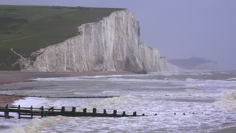 The-sea-breaks-along-wooden-jetties-along-the-shore-of-the-White-Cliffs-of-Dover-at-Beachy-Head-England-1