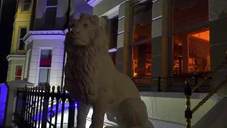 Una-Estatua-De-León-Se-Encuentra-Frente-A-Una-Elegante-Hilera-De-Casas-Y-Un-Pub-En-Una-Ciudad-Británica