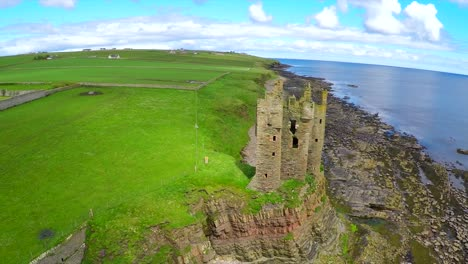 A-beautiful-aerial-shot-over-an-abandoned-castle-along-the-North-Coast-of-Scotland-