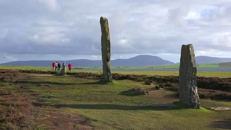 People-walk-near-the-sacred-Celtic-stones-on-the-Islands-of-Orkney-in-Northern-Scotland