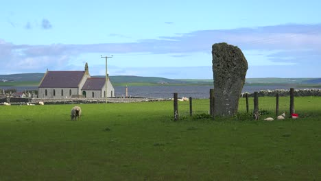 The-sacred-Brodgar-circular-Celtic-stones-on-the-Islands-of-Orkney-in-Northern-Scotland-with-church-background