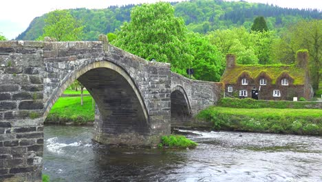 A-beautiful-bridge-over-a-river-with-a-moss-covered-house-in-the-distance-Wales
