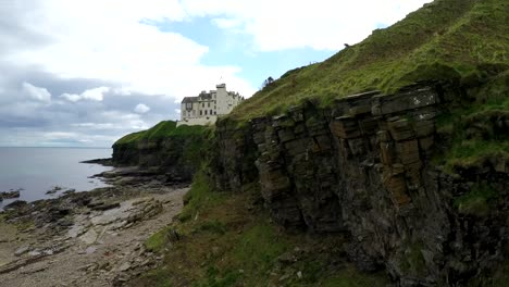 A-rising-aerial-shot-of-a-Scottish-castle-or-estate-along-a-cliff