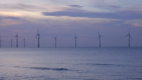 A-wind-farm-generates-electricity-along-a-coastline-at-sunset-1
