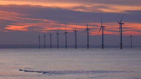 A-wind-farm-generates-electricity-along-a-coastline-at-sunset-2
