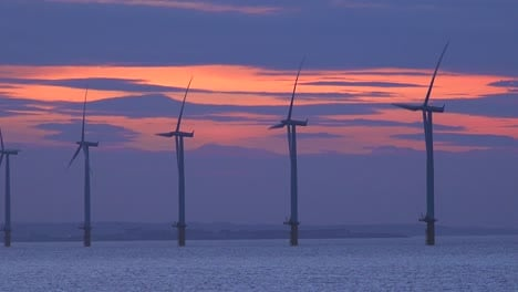 Windmills-generate-electricity-along-a-coastline-at-sunset