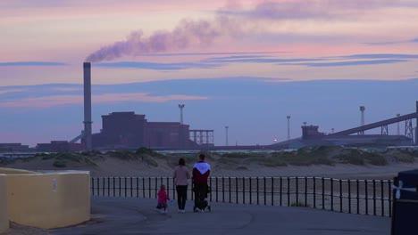 A-power-plant-emits-smoke-along-a-beach-in-England