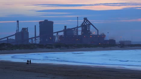 A-power-plant-at-dusk-along-a-beach-in-England-with-people-waking-background