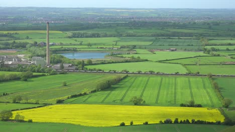 A-freight-train-passes-through-the-fertile-green-countryside-of-England-near-a-power-plant