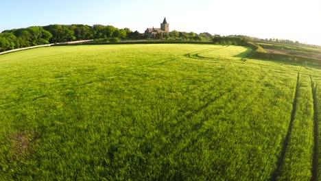 Una-Hermosa-Antena-Sobre-Campos-Amarillos-Con-Una-Iglesia-Distante-En-Inglaterra