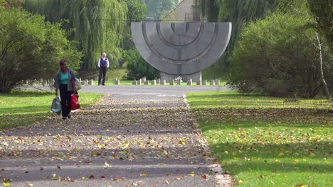 Old-woman-walks-near-a-Jewish-menorah-memorial-at-the-Terezin-Nazi-concentration-camp-in-Czech-Republic