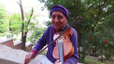 A-colorful-old-gypsy-man-plays-the-violin-in-a-park-in-Budapest-Hungary