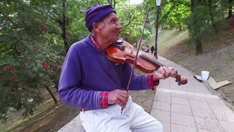 A-colorful-old-gypsy-man-plays-the-violin-in-a-park-in-Budapest-Hungary-1