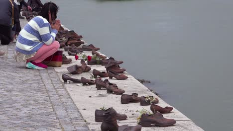 Visitors-remember-victims-of-the-Holocaust-at-the-Shoes-Along-The-Danube-Memorial-in-Budapest-Hungary