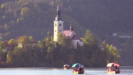 Rowboats-head-for-the-island-on-Lake-Bled-Slovenia-at-sunset