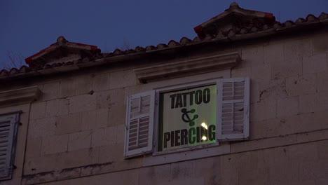 Establishing-shot-of-a-tattoo-and-piercing-studio-in-an-old-rundown-building