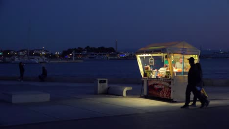Evening-establishing-shot-of-an-hot-dog-food-stall-or-stand-in-Split-Croatia
