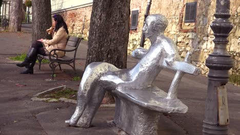 An-artistic-rendition-of-a-person-sitting-on-a-bench-sits-near-a-real-person-sitting-on-a-park-bench