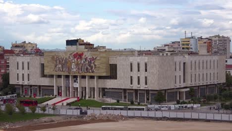 A-view-of-downtown-Tirana-Albania-streets-and-traffic-with-museum-and-revolutionary-Communist-mural-in-distance