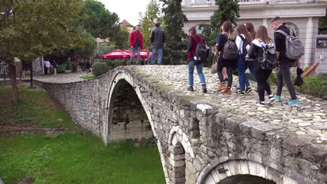 Pedestrians-walk-over-an-old-stone-bridge-in-Tirana-Albania